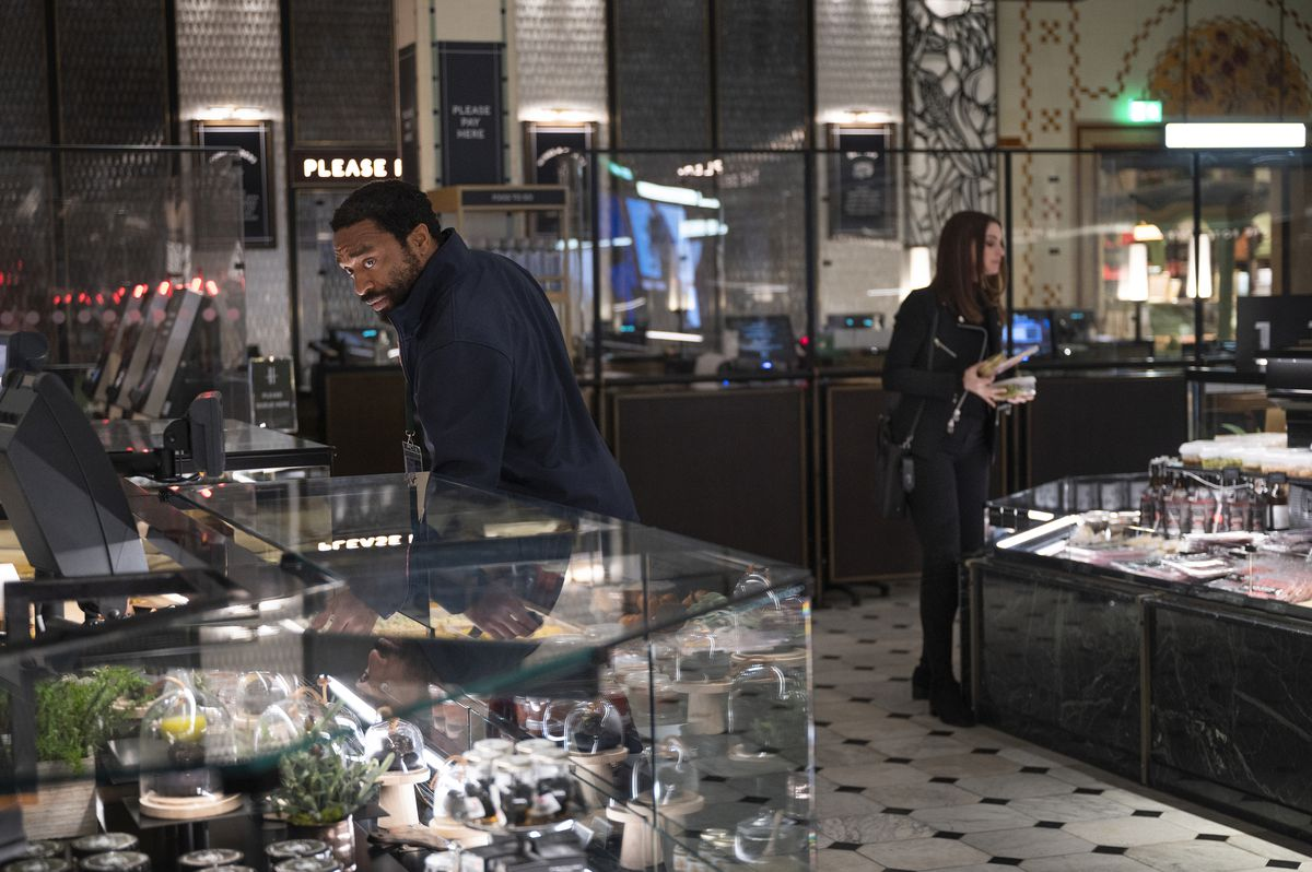 Anne Hathaway and Chiwetel Ejiofor look through the jewelry counter in a store in Locked Down