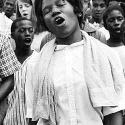 A photo from the exhibit: March participants sing during a Deacons of Defense march through Bogalusa, La. Song was the glue that helped hold the civil rights community together. It fostered courage in times of danger, solidarity in times of stress. Matt Herron, Bogalusa, La., 1965