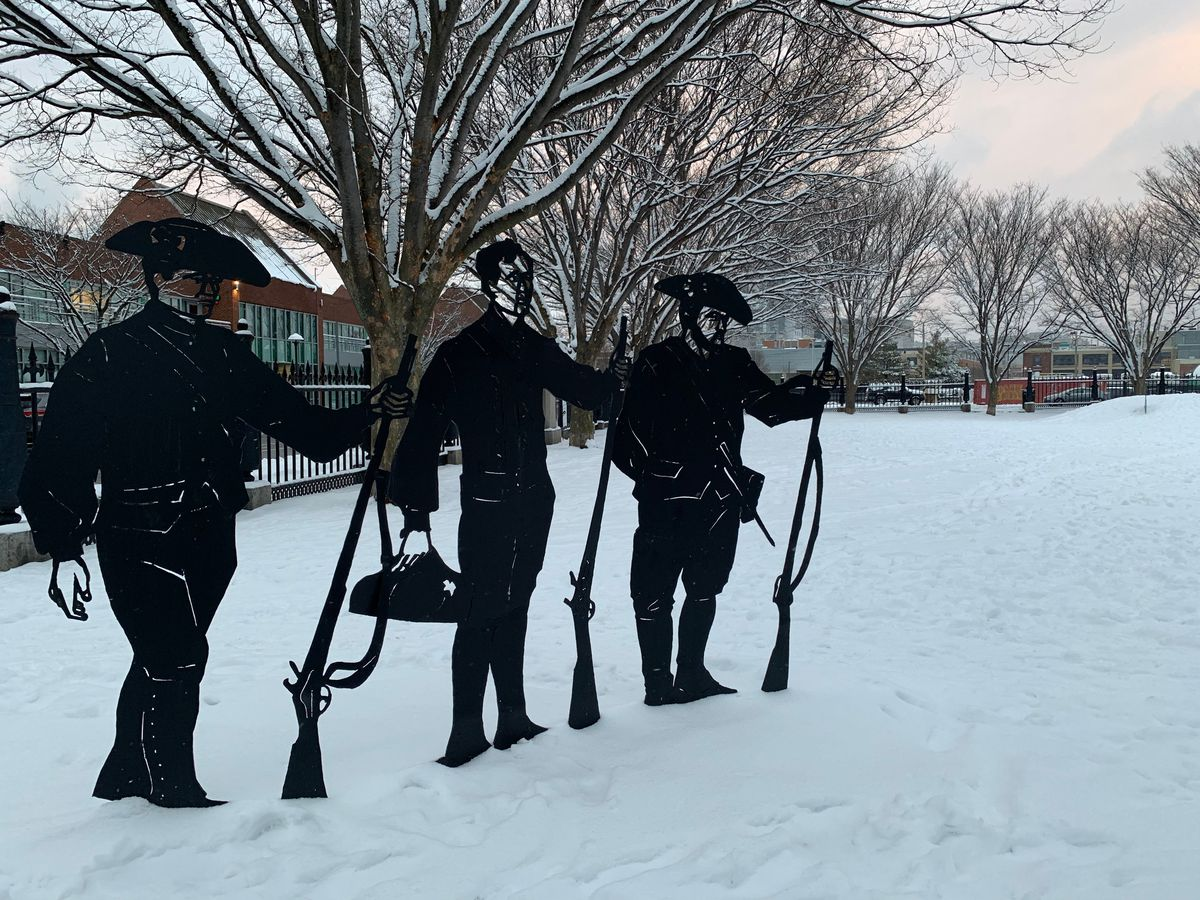 Three steel statues of Revolutionary War soldiers holding muskets in a snow-covered park.