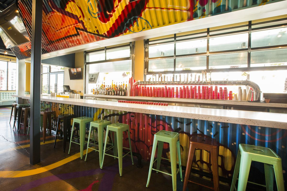 A colorful and empty bar space with stools.