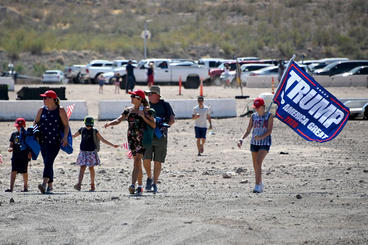 A group of adults and children walks from a parking lot behind them, dressed in summer clothing and carrying a large Trump flag.