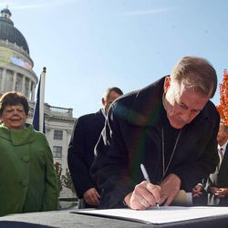 Bishop John C. Wester signs a document known as the Utah Compact during a press conference where community leaders gathered in support of immigration reform at the Sstate Capitol in Salt Lake City Nov. 11, 2010.