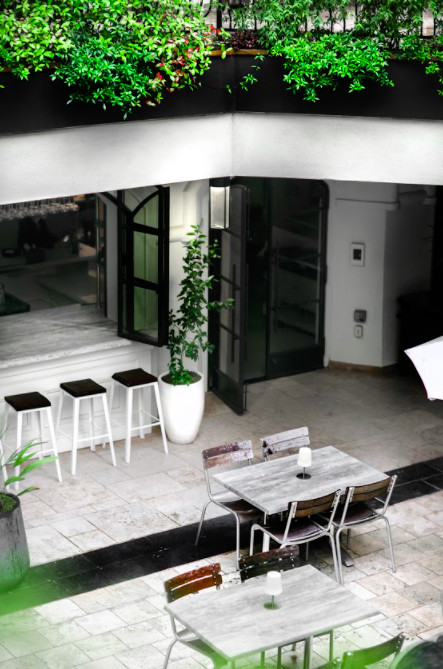 Looking down over the patio at Yebo Beach Haus, two weathered gray tables with four wood and metal chairs sit atop a white stone tile patio floor, a small marble bar features three metal and black top bar stools behind the tables.