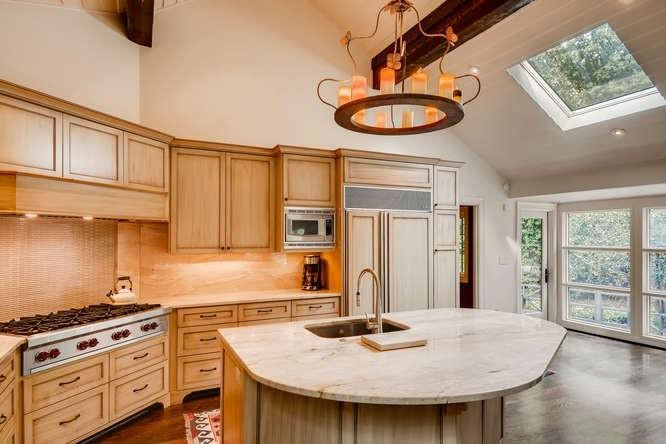 A big white kitchen with light wood cabinetry.