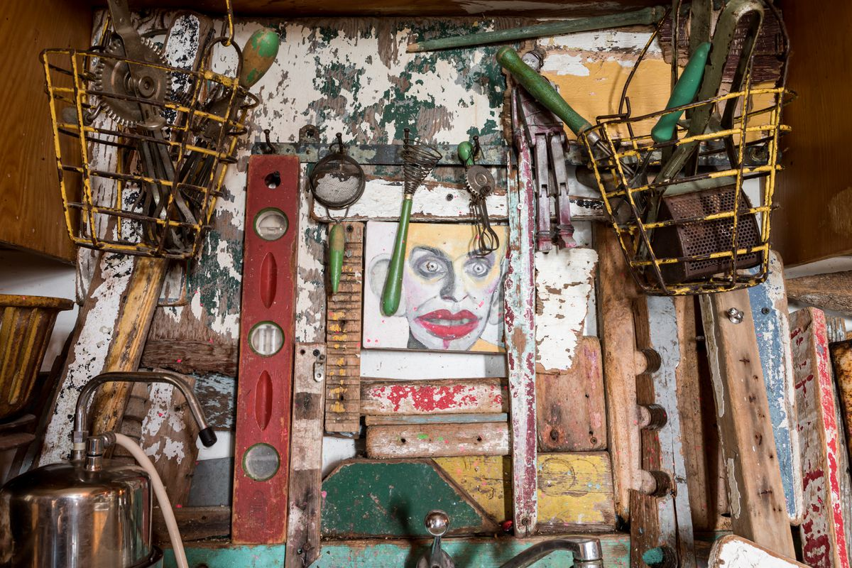 Many objects and works of art hang on a wall with decaying and peeling paint.