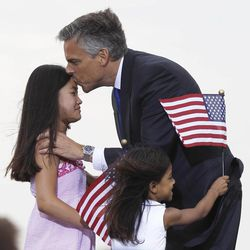 Republican presidential candidate and former Utah Gov. Jon Huntsman Jr. kisses one of his daughters while his other daughter rushes him, after he announced his bid, Tuesday, June 21, 2011, at Liberty State Park in Jersey City, N.J.