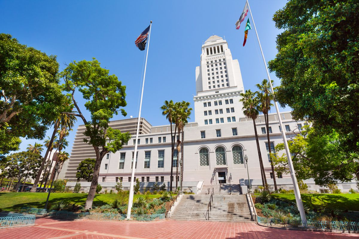 The exterior of Los Angeles City Hall. The facade is white with a tower. There are trees and flagpoles in the foreground.