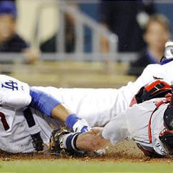 Los Angeles Dodgers' James Loney, left, loses his helmet as he slides safely past St. Louis Cardinals catcher Jason LaRue on an RBI double by Russell Martin.