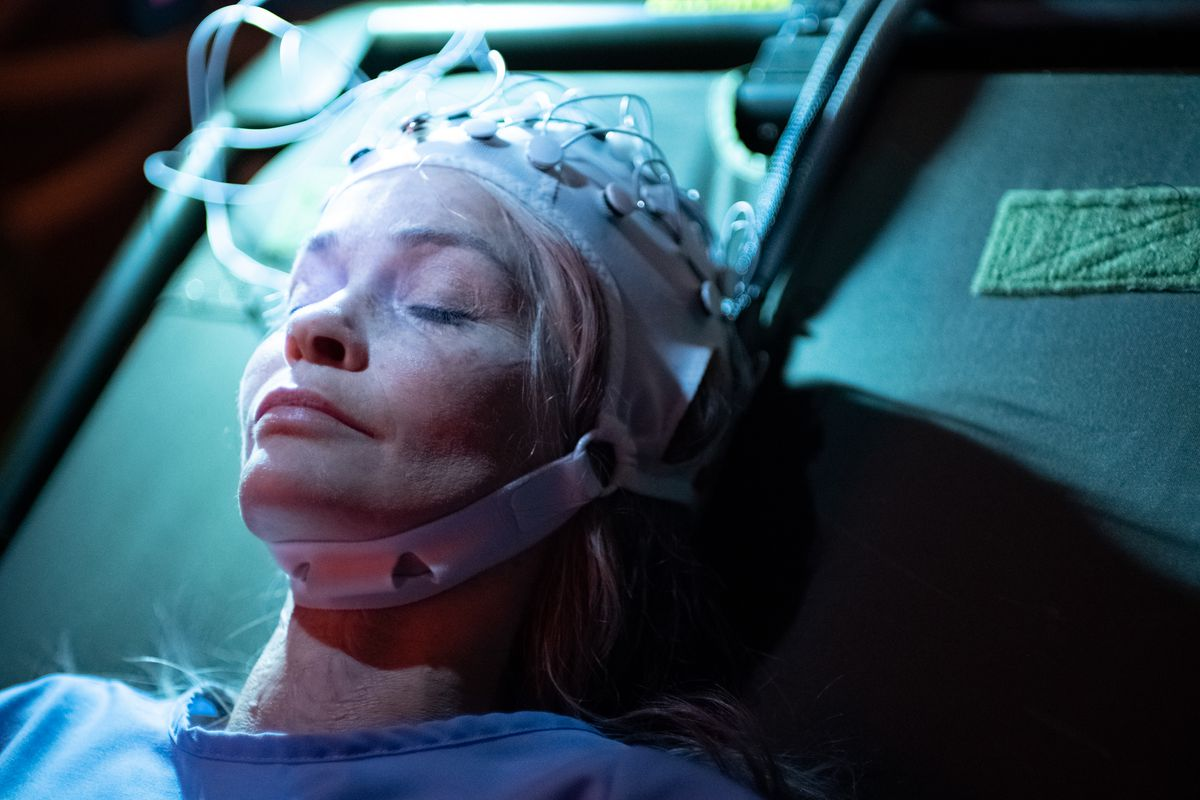Nathalie Boltt laying on a table with a virtual reality helmet on in Demonic