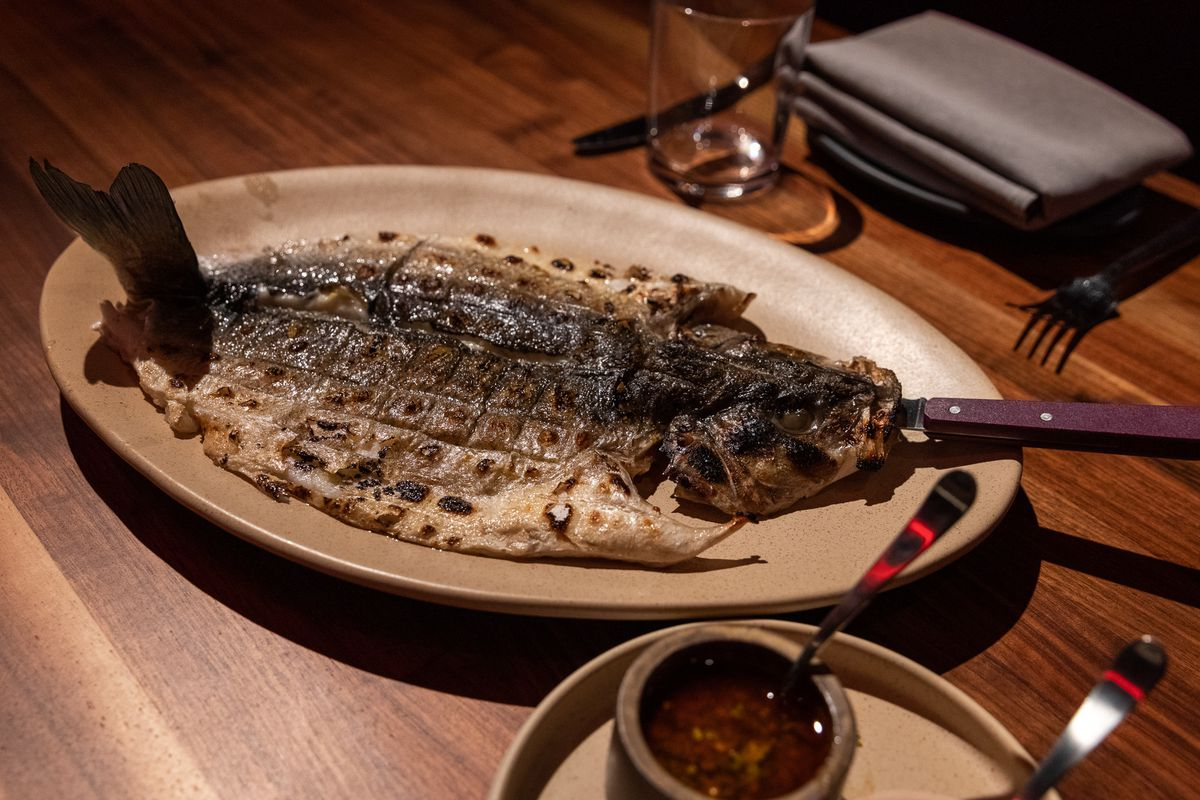 A fish is butterflied with the head and silver skin facing up and a plate of red, oily dip sits next to it.