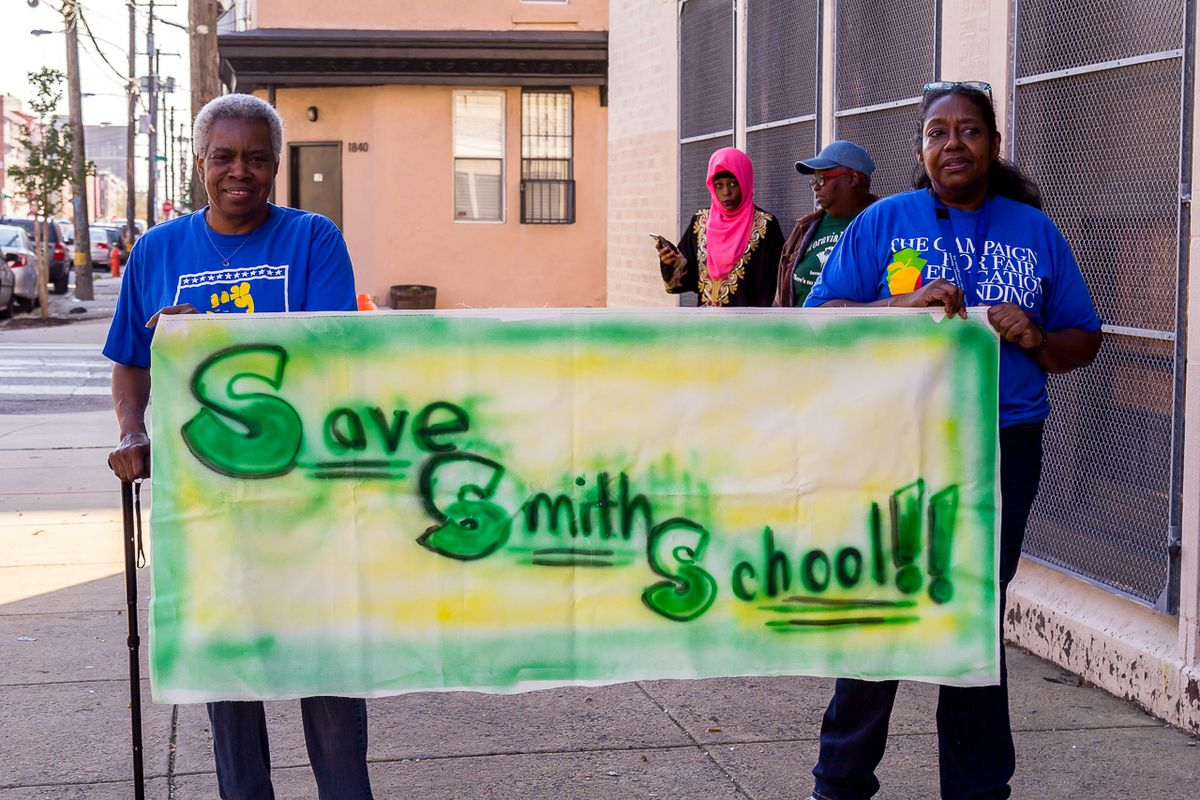 Two people holding a green and yellow banner that reads: Save smith schools.