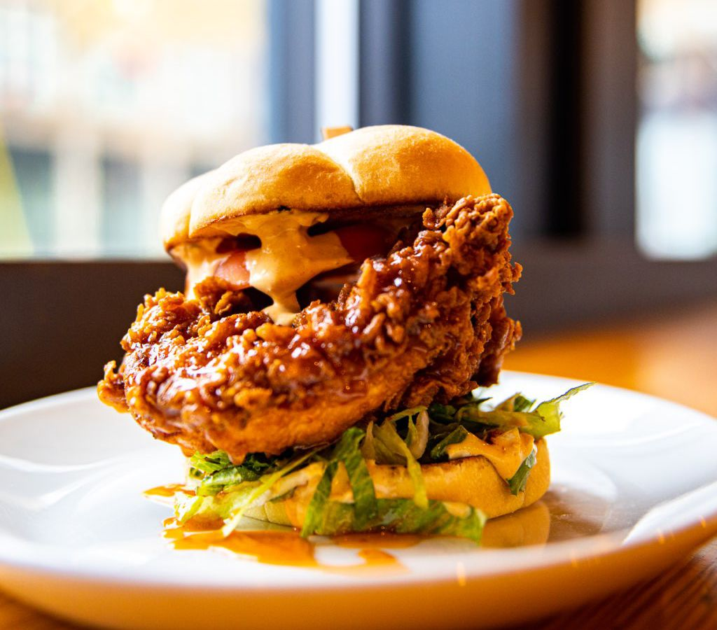 A fried chicken sandwich, with shredded lettuce and sauce, on a plate in front of a sunny window