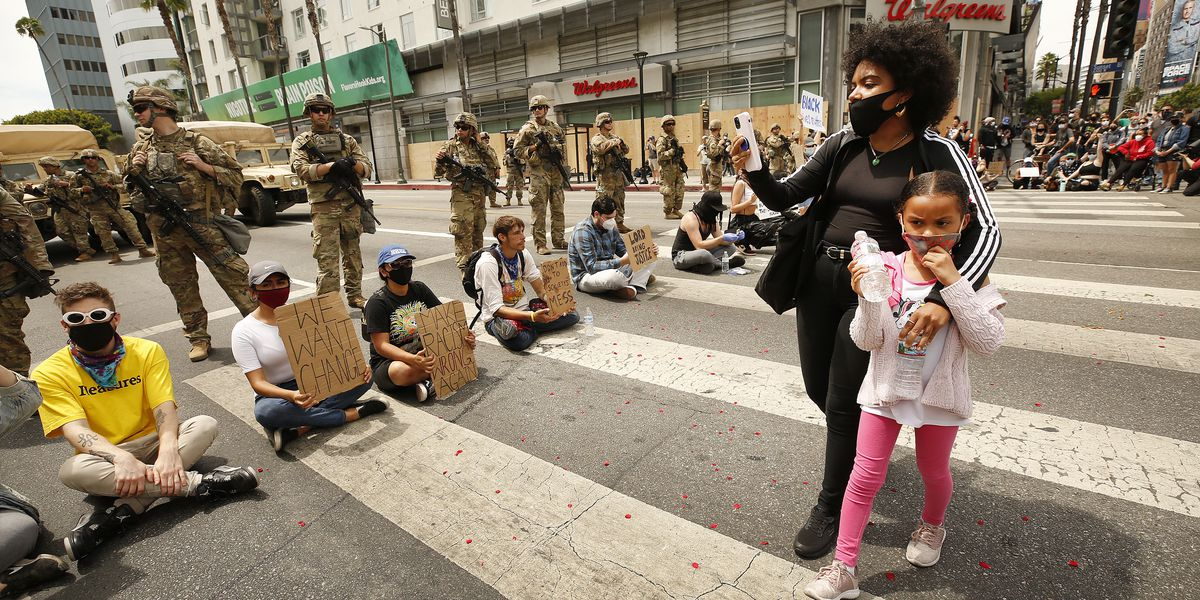 A mother who brought her daughter uses her phone as she walks past protesters siting in the street in front of National Guardsmen as they stand guard closing Sunset Blvd at Vine Street in Hollywood on June 2.