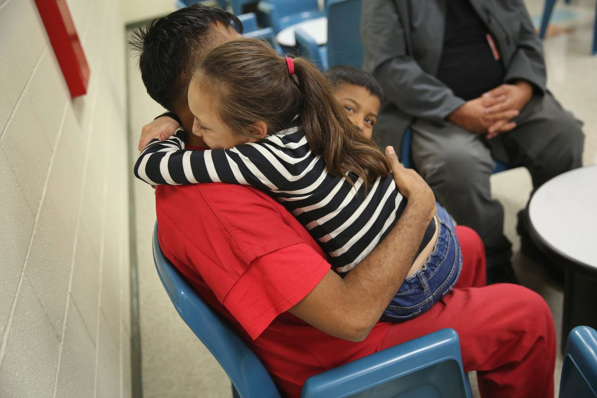 child hugging detainee father