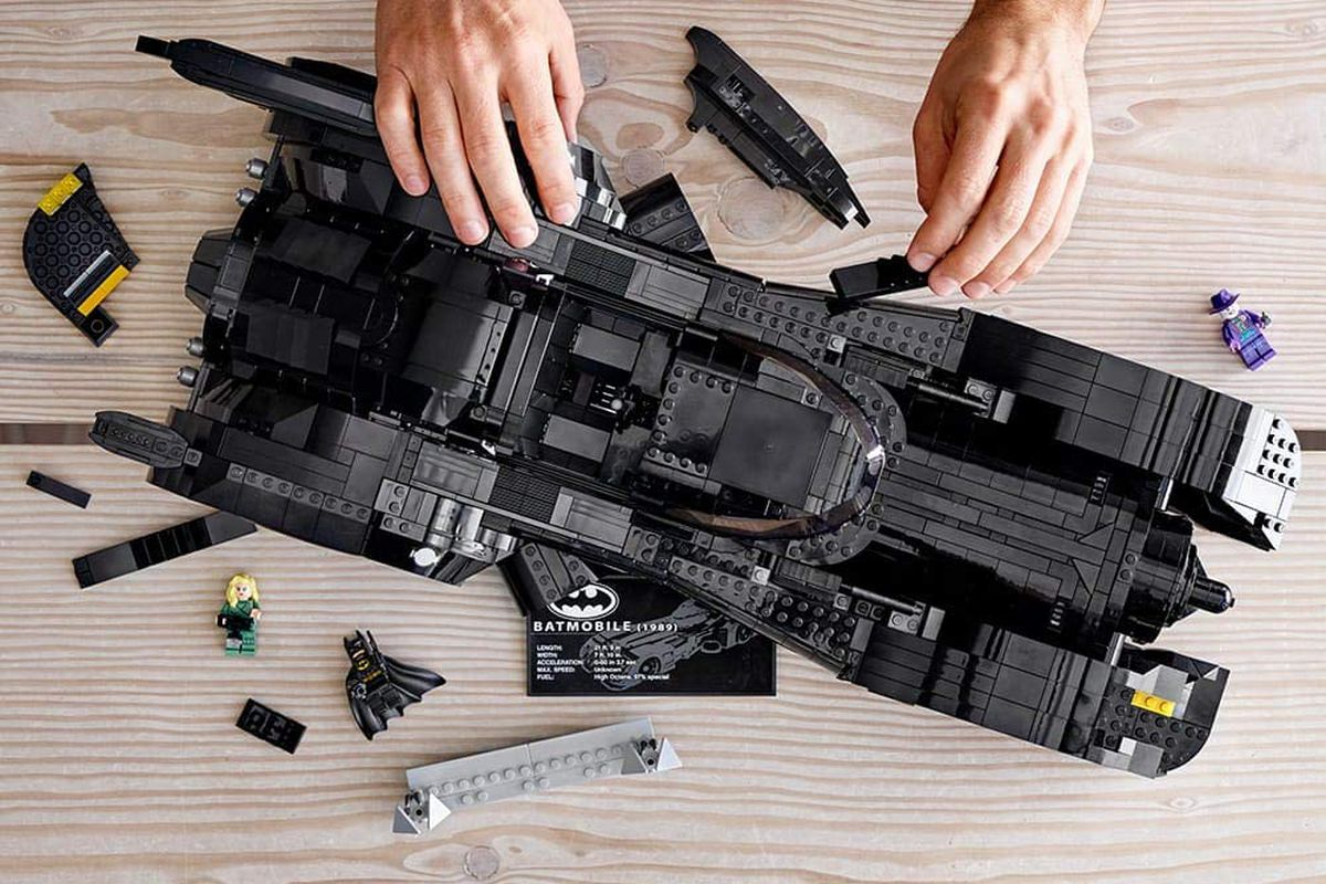Hands constructing the Lego Batmobile set