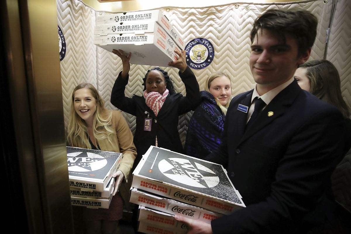 People in an elevator holding pizza boxes.
