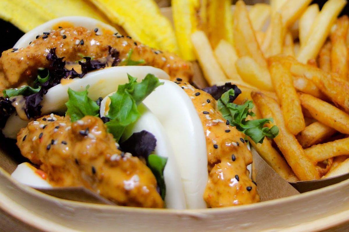 A plate of bao buns next to a pile of fries. The buns are filled with chicken coated in a creamy-looking sauce and topped with sesame seeds