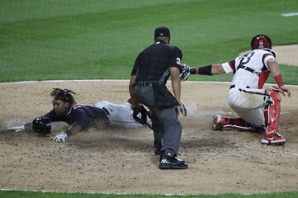 The Indians' Jose Ramirez scores on a Delino DeShelds bunt as White Sox catcher James McCann applies a late tag during the 10th inning.
