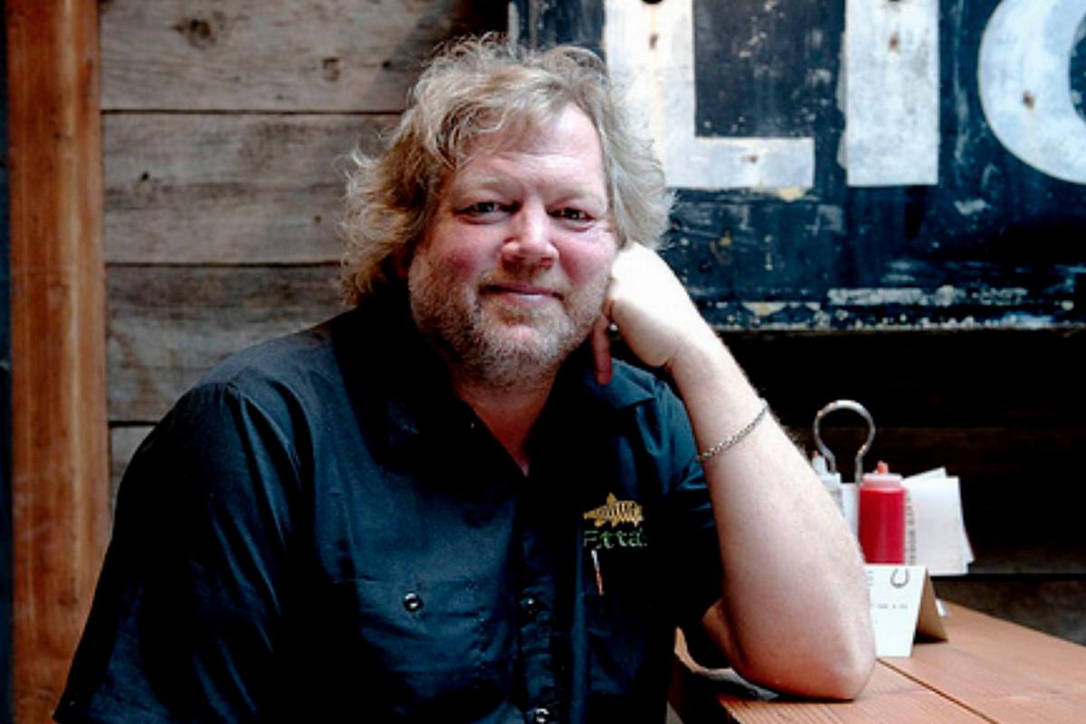 Chef Tom Douglas leans against a table.