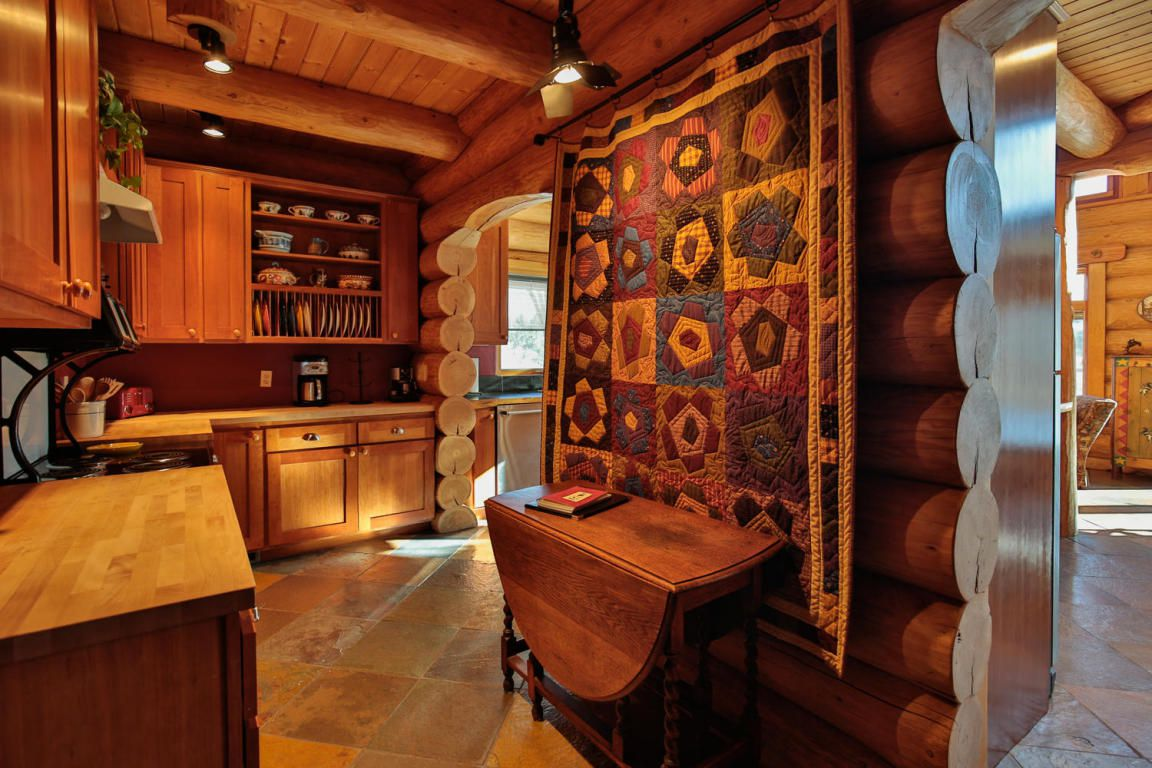 A kitchen in a log lodge. A quilt with a patchwork floral pattern hangs on the right wall.