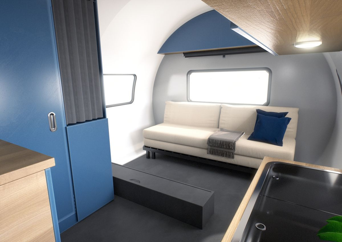 The interior of the camper features blue and silver walls, a white futon sofa, and a window.
