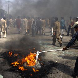 Pakistani protesters burn tires to block the main highway in Rawalpindi, Pakistan on Friday, Sept. 21, 2012. Pakistan has blocked cell phone service in major cities to prevent militants from using phones to detonate bombs during a national day of protest against an anti-Islam film produced in the United States.