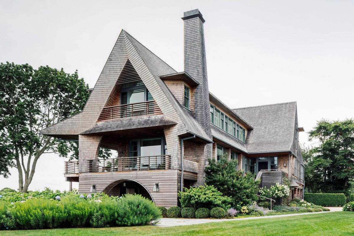 This shingled house has a traditional, peaked roof with modern angles on the gable and overhang.