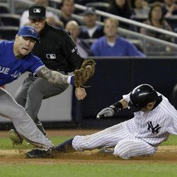Toronto Blue Jays third baseman Brett Lawrie, left, stretches to catch the throw as New York Yankees' Ichiro Suzuki, right,steals third in the eighth inning of Game 2 of a baseball doubleheader at Yankee Stadium in New York, Wednesday, Sept. 19, 2012.  Suzuki had four stolen bases and the winning hit in the Yankees' 2-1 victory.