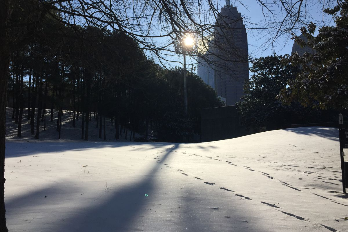 A snowy hill with footprints and buildings beyond.