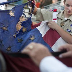 An old American flag with 48 stars is folded at a retirement ceremony at the Davis County Fair in Farmington on Thursday, Aug. 15, 2013. Participants in the ceremony included the American Legion, Utah National Guard, Boy Scouts and Girl Scouts, and members of Davis County fire departments.