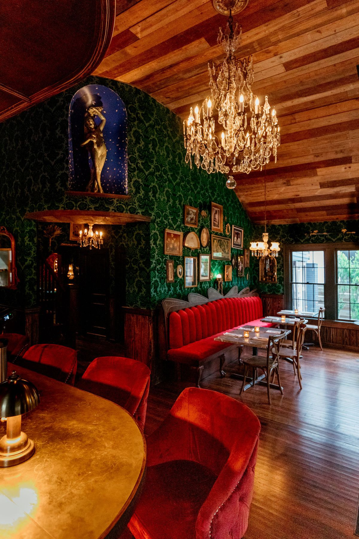 wood ceiling, chandelier, forest green wallpaper, red booth, very New Orleans vibes
