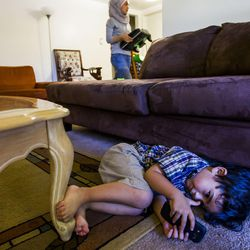 Zain Bilal, 3, plays on a phone while his sister, Nour, 15, does homework at their home in Millcreek on Tuesday, Sept. 8, 2015.