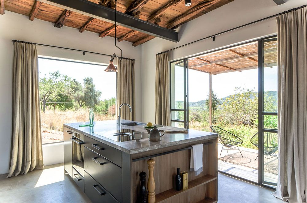 Kitchen island facing large windows