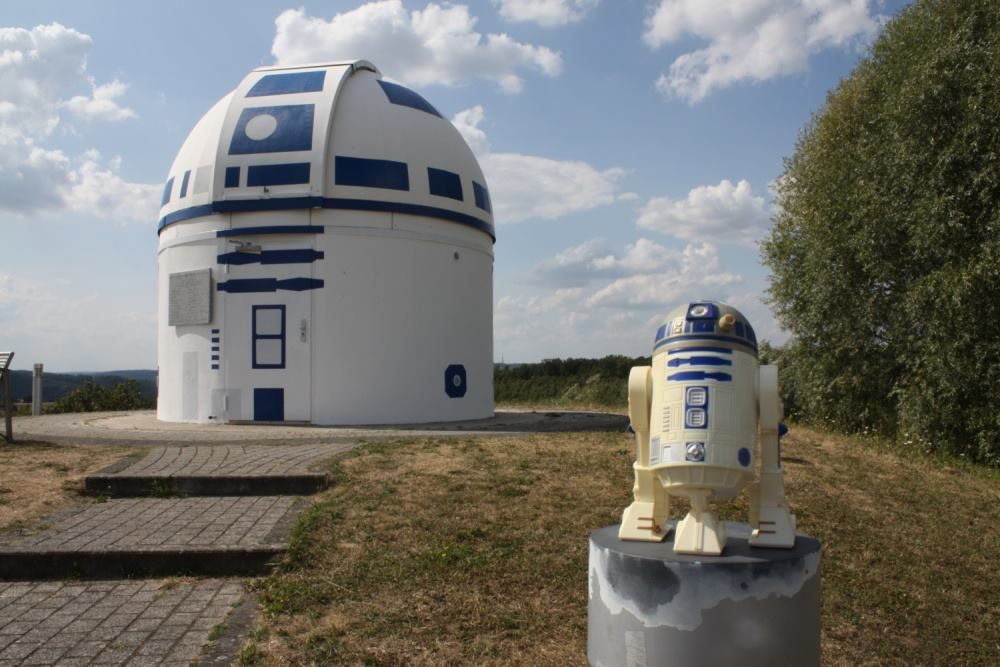 An observatory painted to resemble R2-D2 from Star Wars has a toy R2-D2 sitting in front of it.