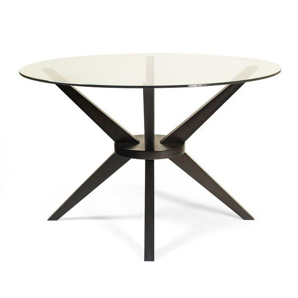 """A round table with a glass top and wooden legs that form an """"X"""" brace when viewed from any side."""