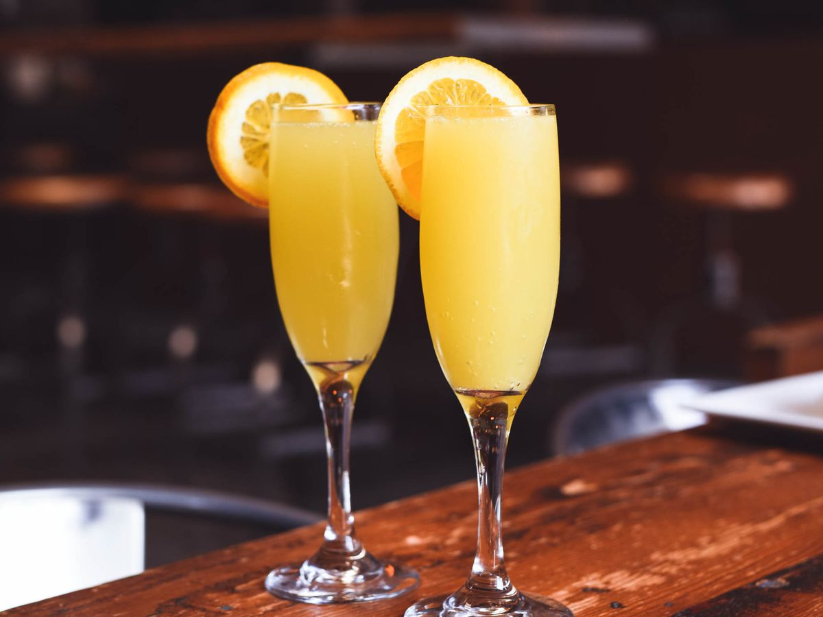 Two mimosas in champagne flutes on a wooden table with sliced orange garnish on the rim.