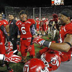 Utah Utes wide receiver DeVonte Christopher (10),  Dres Anderson (6) and Reggie Dunn (14) , from left, celebrate as the University of Utah and Brigham Young University play football Saturday, Sept. 17, 2011, in Provo, Utah.