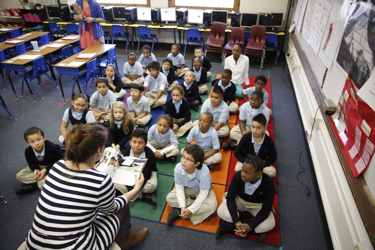 Young students in matching school uniforms sit criss-cross-applesauce on a colorful rug. They are facing the camera. A teacher with her back to the camera reads the students a book.