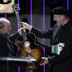 Richard Thompson, right, receives a Gibson guitar from Dave Berryman, president of of Gibson Guitar Corp. after being awarded the Lifetime Achievement Songwriting Award at the 11th annual Americana Honors & Awards, Wednesday Sept. 12, 2012, in Nashville, Tenn.
