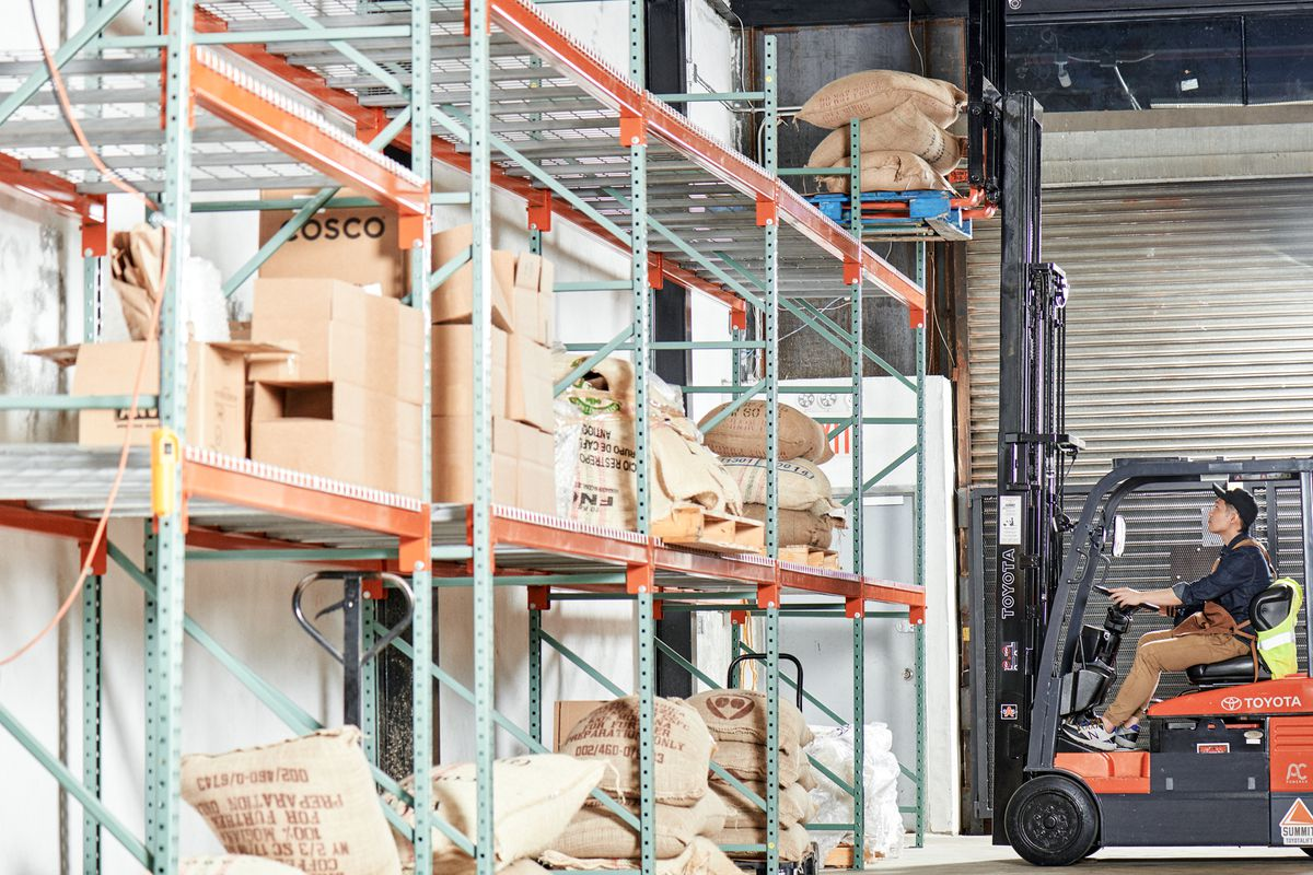 A forklift can be seen trying to lift coffee bags on shelves placed along the wall inside Shared Roasting