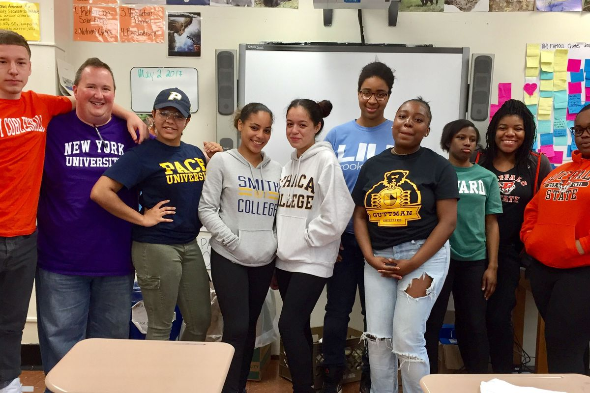 Steven Serling, wearing a New York University shirt, poses with seniors wearing gear to represent the colleges they've committed to attending.