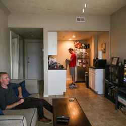 Connor Reese, 24, left, and his roommate, Cole Thomas, 33, hang out and watch the University of Utah football game at their apartment on First Avenue in Salt Lake City on Saturday, Oct. 1, 2016.