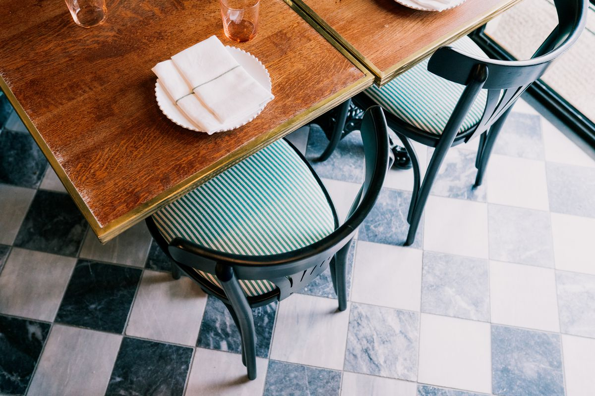 Black wooden chairs with curved backs and striped green and white upholstered seats are placed at wood tables and shown from above against the checkerboard patterned floors.