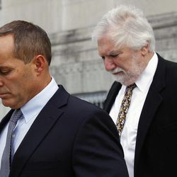 Andrew Young, former aide to former U.S. Sen. and presidential candidate John Edwards, leaves federal court with attorney David Geneson, right, in Greensboro, N.C., Monday, April 23, 2012. Prosecutors and defense lawyers began making their case to jurors on whether the former presidential candidate violated federal campaign finance laws.