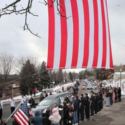 Onlooks stand under a U.S. flag as the funeral procession for Unified police officer Doug Barney makes its way to the Orem City Cemetery on Monday, Jan. 25, 2016. Barney was killed in the line of duty on Jan. 17, 2016.