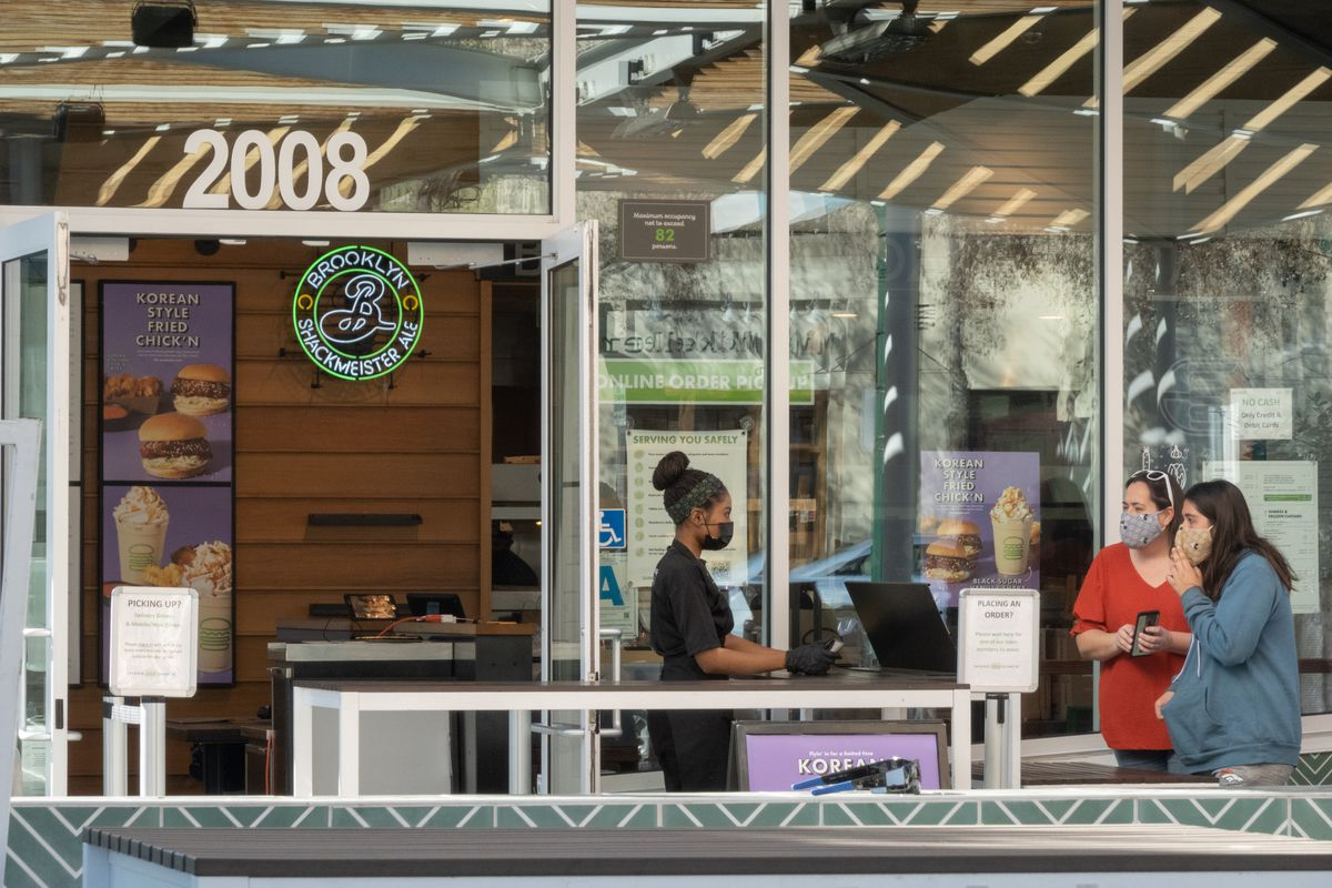 A black restaurant worker wearing a mask takes orders from two woman at a register outside of Shake Shack in California.
