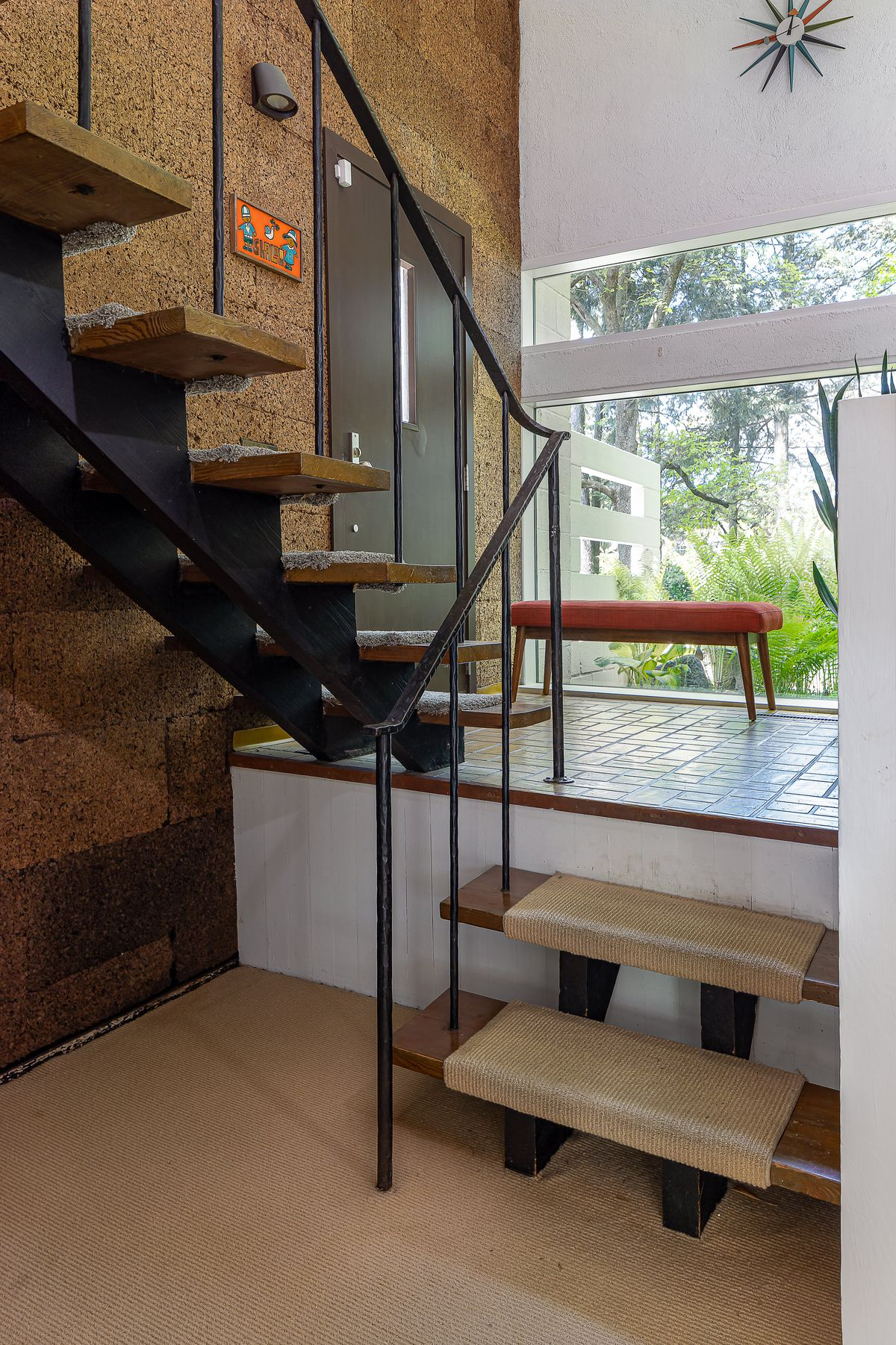 A foyer with glass walls and stairs that go upwards next to cork walls.