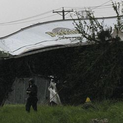 A man walks beneath the trailer of an 18-wheeler that sits atop a tree and a power line pole after a tornado swept through the area Tuesday, April 3, 2012, in Lancaster, Texas. Tornadoes tore through the Dallas area Tuesday, peeling roofs off homes, tossing big-rig trucks into the air and leaving flattened tractor trailers strewn along highways and parking lots.