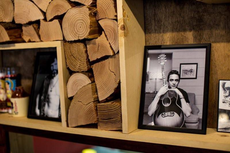 A black and white photo of Johnny Cash on display next to wall of chopped wood.