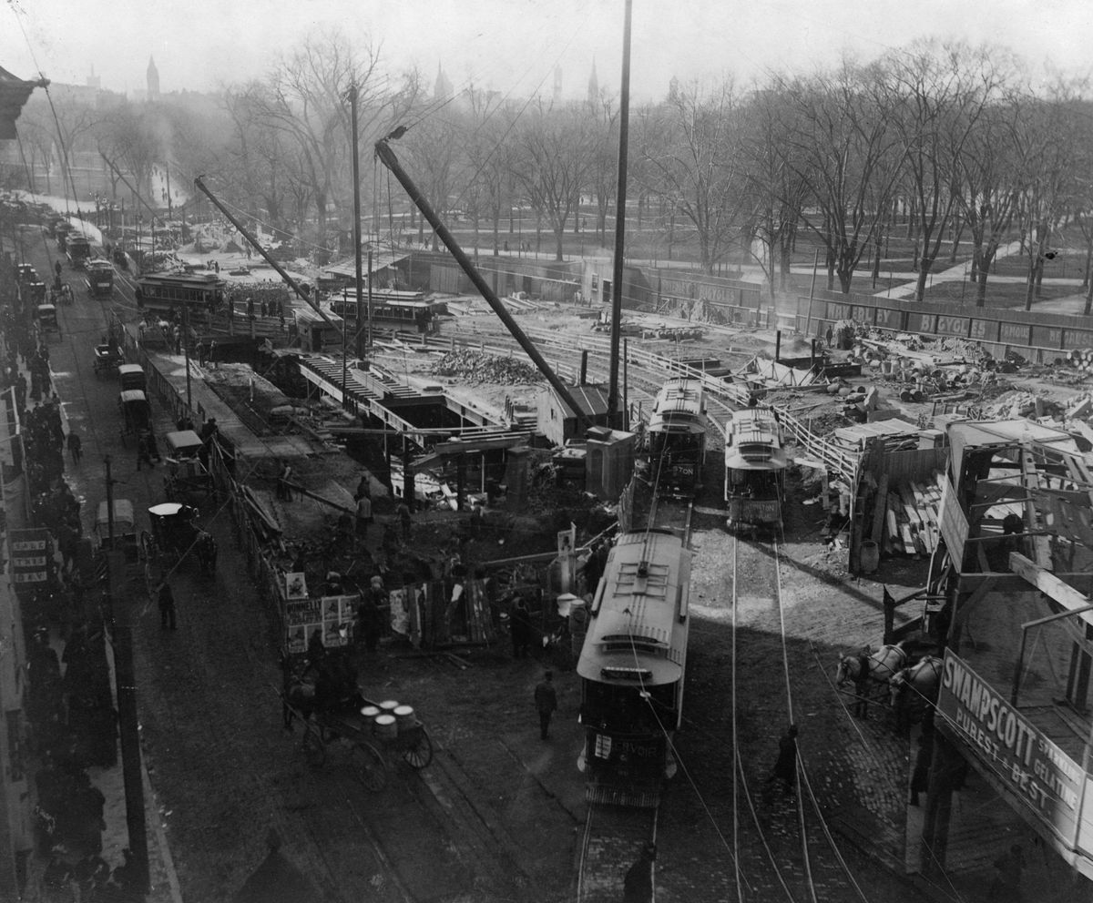 An old photograph of streetcars making their way past a public park in a city.